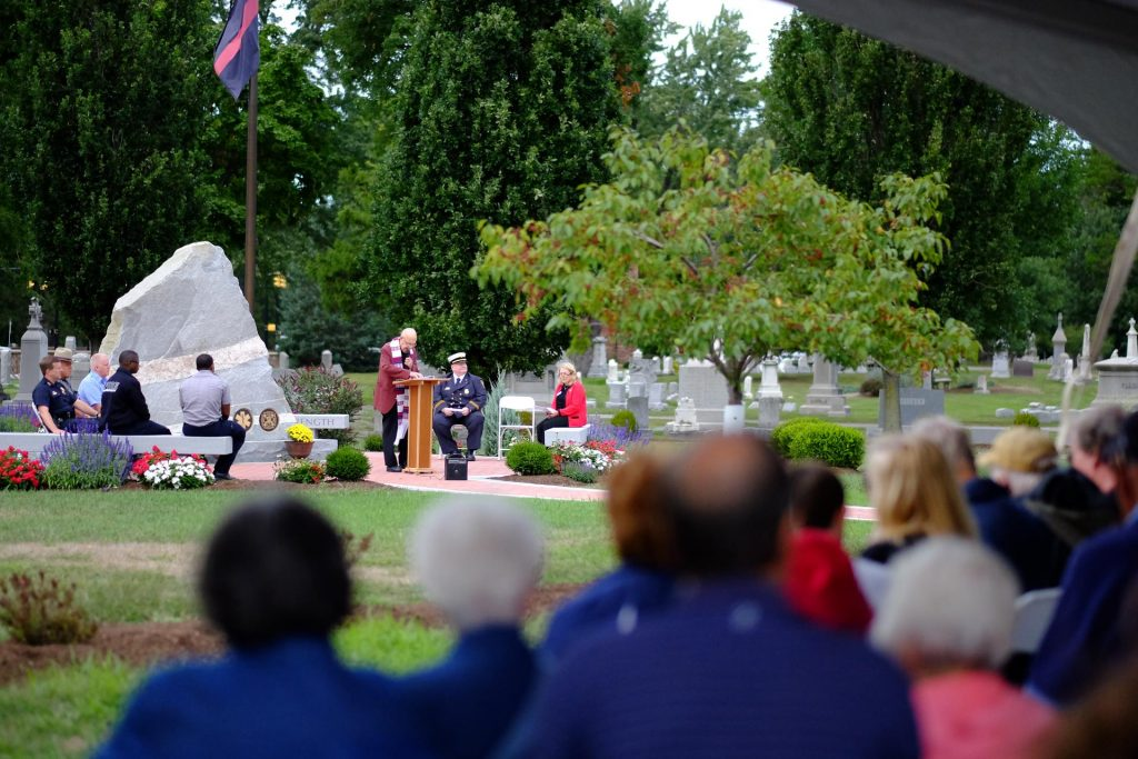 service for a first responder in front of a large monument
